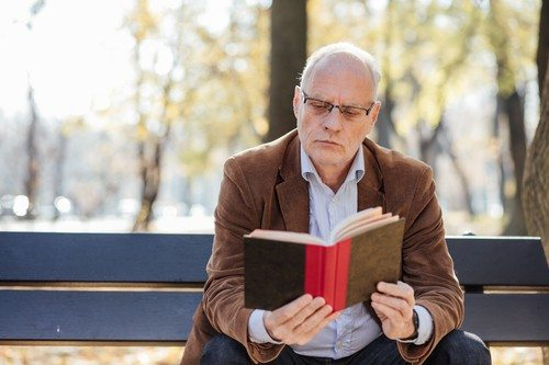 old elegant man reading a book outside