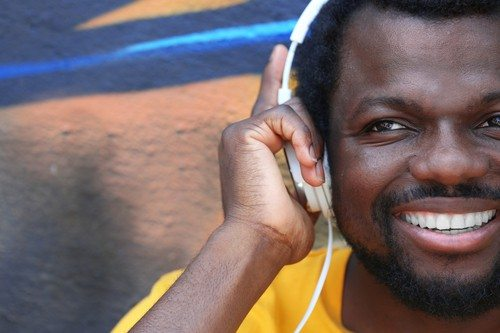 African American man listening music with headphones near graffiti wall outdoors